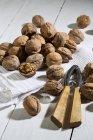 Весь і тріщинами волоські горіхи з Лускунчик і блюдо рушник на білий дерев'яний стіл — стокове фото