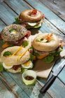 Four different bagels garnished with salami, slices of bacon, rocket salad, tomato, lettuce, cucumber carrot, egg, cream cheese and cress and parsley — Stock Photo