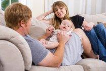 Улыбающиеся родители с маленьким мальчиком, сидящим на диване — стоковое фото