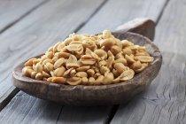 Pelle en bois avec arachides pelées sur la surface en bois — Photo de stock