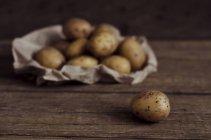 Frische Kartoffel auf dunklem Holz mit Haufen von Kartoffeln mit Papier auf Hintergrund — Stockfoto