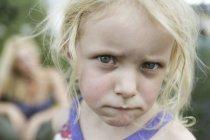 Ritratto di ragazza che morde le labbra mentre sua madre sullo sfondo, da vicino — Foto stock