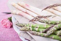 Asperges vertes et blanches sur plaque avec fleur sur la nappe rose — Photo de stock
