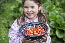 Portrait of smiling girl holding bowl of fresh picked strawberries — Stock Photo