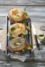 Three different bagels garnished with salami, sausage, slices of bacon, rocket salad, lettuce, cucumber carrot, egg, cream cheese and cress and parsley — Stock Photo