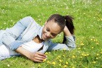 Усміхаючись молоду жінку, лежачи на Луговий квітка — Stock Photo