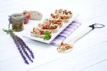 Teller mit Bruschetta mit Tomaten, Shimeji Pilze und Kräuter auf Holztisch — Stockfoto