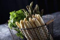 Bouquet d'asperges vertes et blanches avec des herbes dans panier métallique — Photo de stock