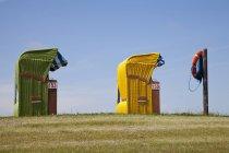 Alemania, Baja Sajonia, Frisia Oriental, Butjadingen, Burhave, dos sillas de playa de mimbre techadas - foto de stock