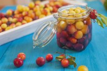 Mirabelle plums in jar for preserving on blue wooden table — Stock Photo