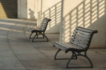 Germany, Berlin, Benches and shadow of man in background — Stock Photo