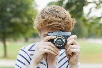 Молодой человек фотографируется в парке на старомодную камеру — стоковое фото