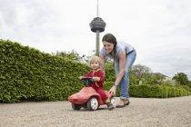 Мати, несучи дочка в машині іграшку, посміхаючись — стокове фото
