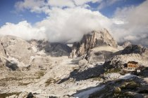 Italy, South Tyrol, Dolomites, Alta Pusteria, Mountainscape with mountain hut under clouds — Stock Photo