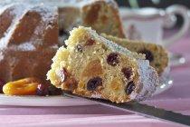 Scheibe hausgemachter Ringkuchen mit Preiselbeeren und Aprikosen mit Puderzucker auf dem Messer — Stockfoto