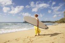 США, Гаваї, жінка, стоячи з дошки для серфінгу на пляжі — стокове фото