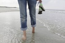 Germany, Lower Saxony, East Frisia, Langeoog, legs of a woman walking at the beach — Stock Photo