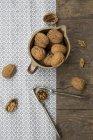 Глиняная посуда кувшин с грецкими орехами и Щелкунчик на деревянный стол со скатерти — стоковое фото