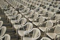 Filas de sillas de plástico blancas bajo la luz solar - foto de stock