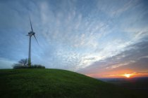 Alemania, Baden-Wuerttemberg, Korntal-Muenchingen, Gruener Heiner, molino de viento al atardecer. - foto de stock