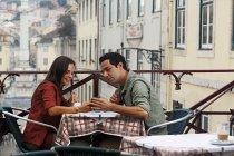 Portugal, Lisboa, Carmo, Largo du Duque, young couple sitting at street cafe — Stock Photo