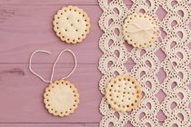 Butter cookies with peekaboo design on crochet tablecloth — Stock Photo