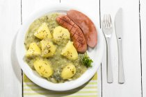 Green cabbage with sausage and potatoes in plate, close up — Stock Photo