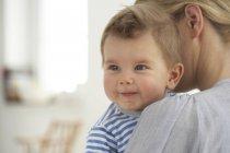 Smiling Baby junge und seine Mutter umarmt — Stockfoto