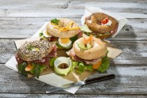 Four different bagels garnished with salami, sausage, slices of bacon, rocket salad, tomato, lettuce, cucumber carrot, egg, cream cheese and cress and parsley — Stock Photo