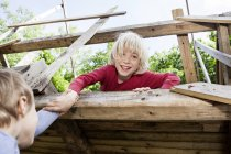 Boys playing in playground at wooden tree house — Stock Photo