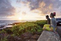 Etats-Unis, Hawaï, Couple adulte moyen regardant le coucher du soleil par la mer — Photo de stock
