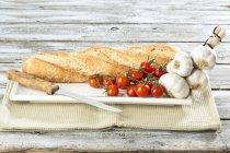 Baguette con pomodori e aglio il vassoio sulla tavola di legno squallido — Foto stock