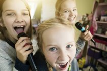 Close-up of Three girls singing with microphones — Stock Photo