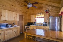 Rustic log home cabin interior with kitchen and dining area — Stock Photo