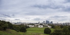 UK, London, Docklands, view to financal district with lawn on foreground during daytime — Stock Photo