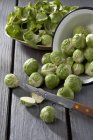 Bowl of Brussels sprouts with peels and knife on grey wooden table — Stock Photo