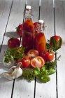 Close-up de duas garrafas de suco de tomate caseiro com tomates frescos na mesa de madeira — Fotografia de Stock