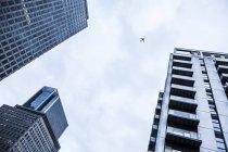 Parti di tre edifici in distretto finanziario e dell'aeroplano nel cielo sopra, Docklands, Londra, Regno Unito — Foto stock