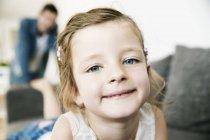 Ritratto di giovane ragazza sorridente sdraiata sul divano, suo padre in piedi sullo sfondo — Foto stock
