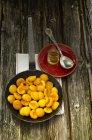 Les abricots caramélisés à la poêle avec le pot d'huile et la cuillère sur la table en bois, gros plan — Photo de stock