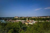 Німеччина, Баварія, Burghausen, міський пейзаж з замку та костелу, зелені дерева на передньому плані — стокове фото