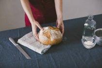 Mãos femininas segurando pão caseiro pão na toalha de cozinha — Fotografia de Stock
