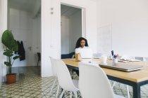 Giovane donna che utilizza il computer portatile in ufficio moderno — Foto stock