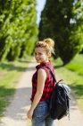 Portrait de femme souriante avec sac à dos dans la nature — Photo de stock