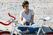 Jeune femme souriante avec vélo et café à emporter — Photo de stock