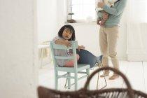 Маленька азіатських дівчина сидить на стілець, матір'ю і сестрою у фоновому режимі — стокове фото