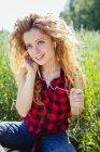 Portrait de femme assise dans un champ entendant de la musique avec des écouteurs — Photo de stock