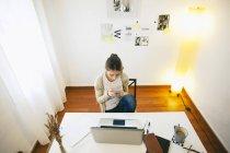 Donna seduta con smartphone al moderno home office — Foto stock