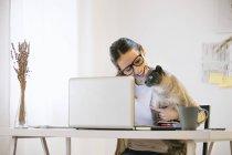 Donna seduta alla scrivania con gatto e portatile — Foto stock