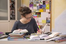 Femelle élève fait ses devoirs au bureau avec une pile de livres — Photo de stock